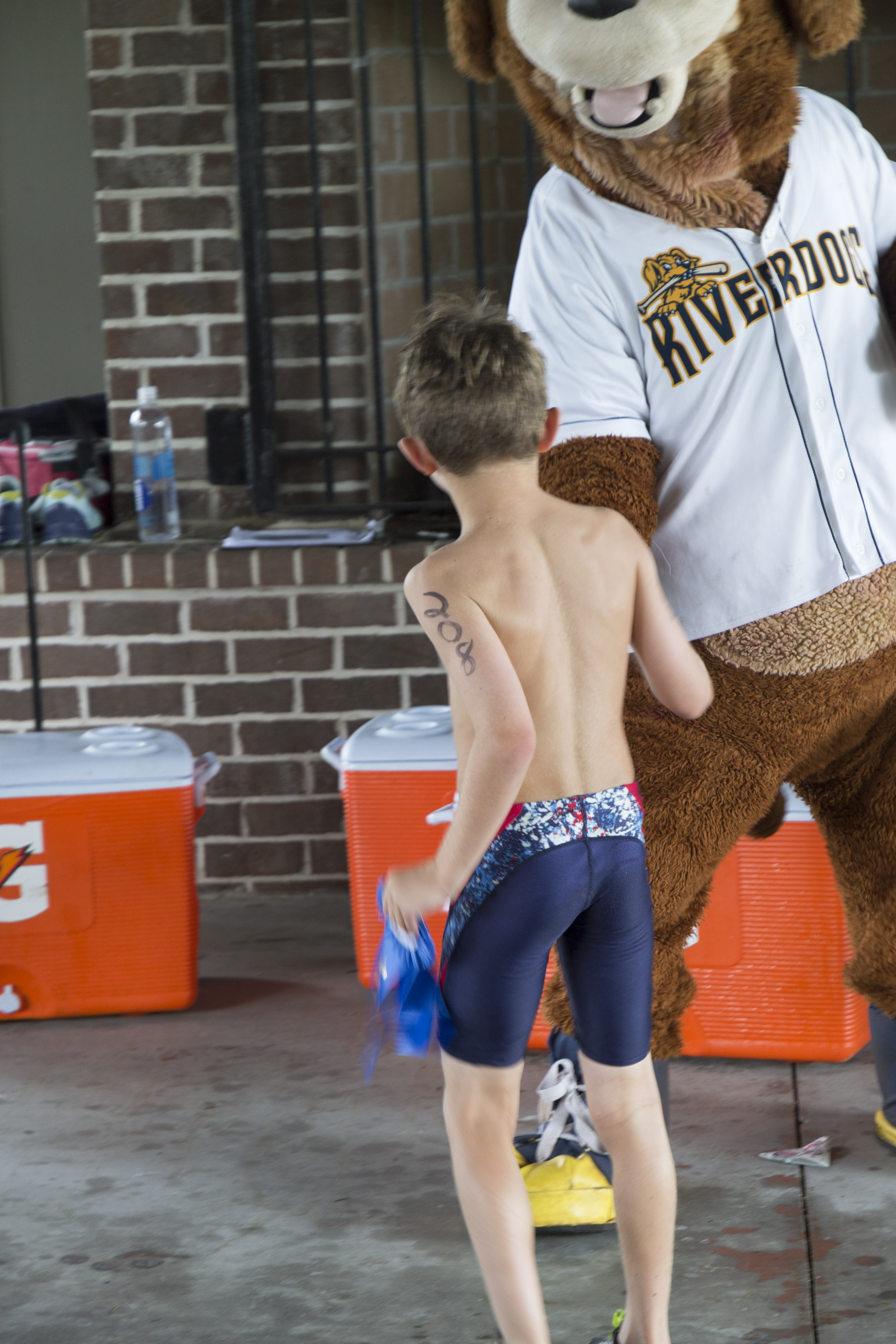 """Jack Ham, who finished first in the 7-8 boys' division, shakes hands with """"Charlie,"""" the Charleston Riverdogs mascot"""