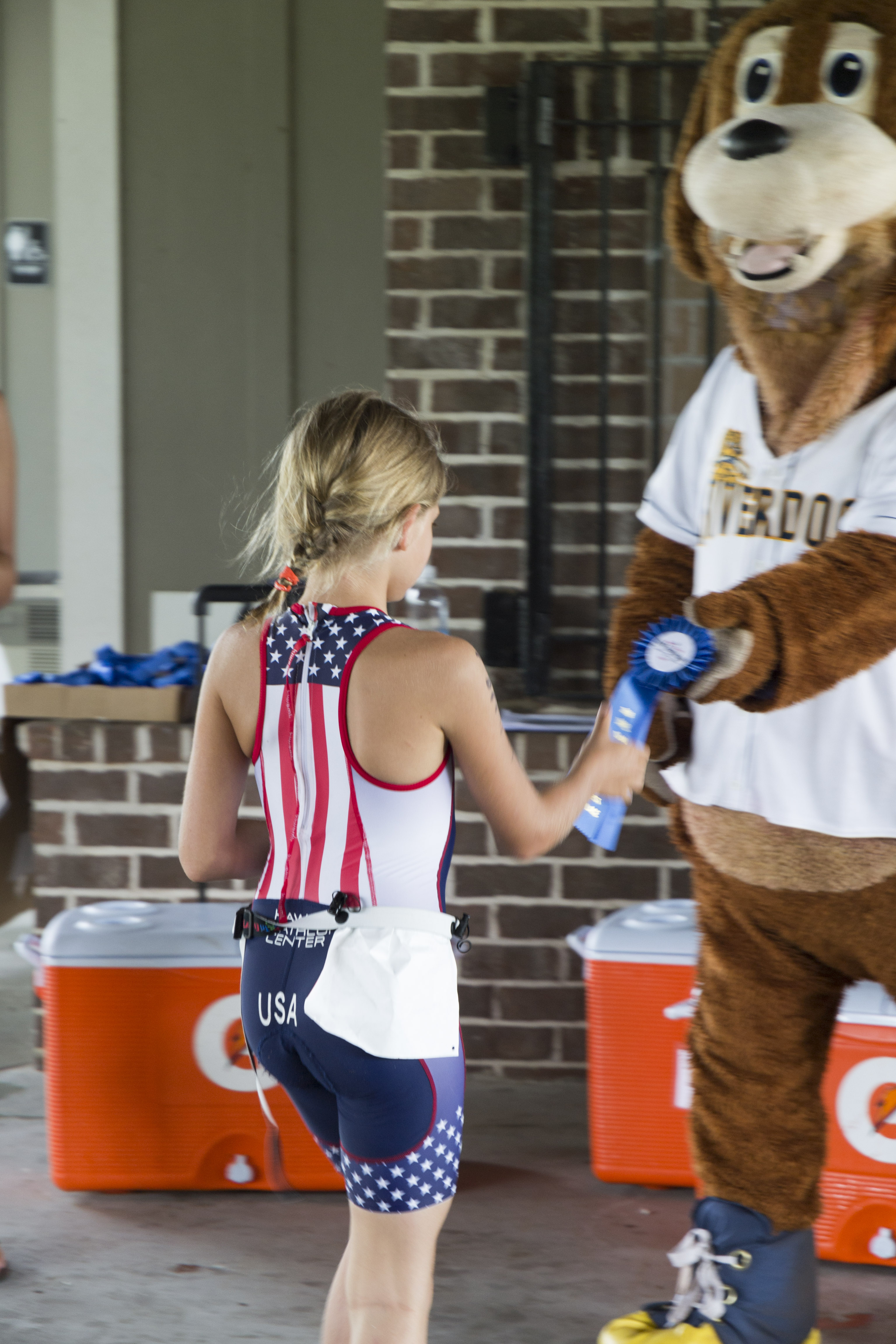 The Charleston Riverdogs mascot gets a handshake from Alaina Harris, the first place winner in the 9-10 girls' age group.