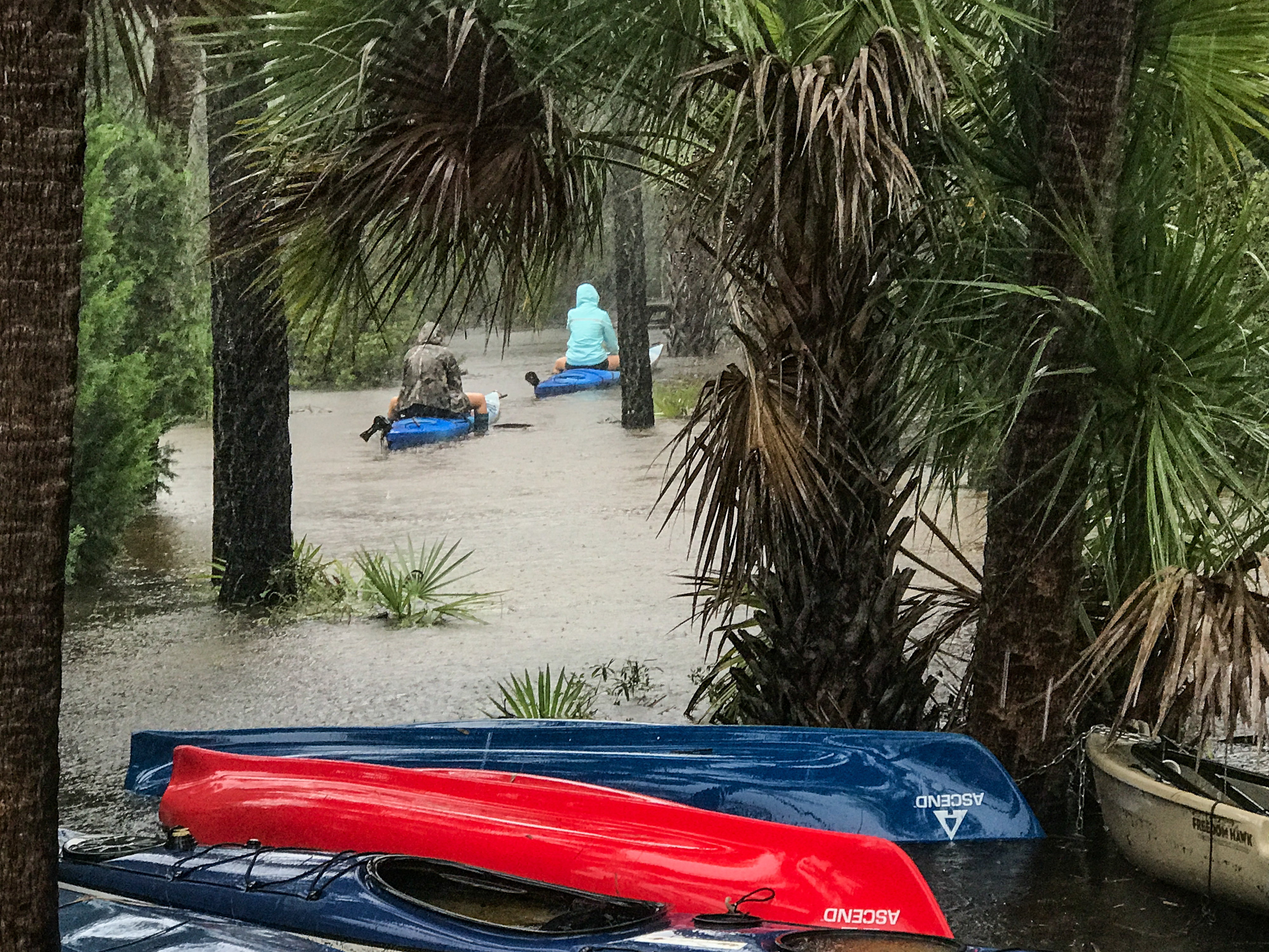 Mary Wessner Photography Kayakers float along what is normally a dirt path.