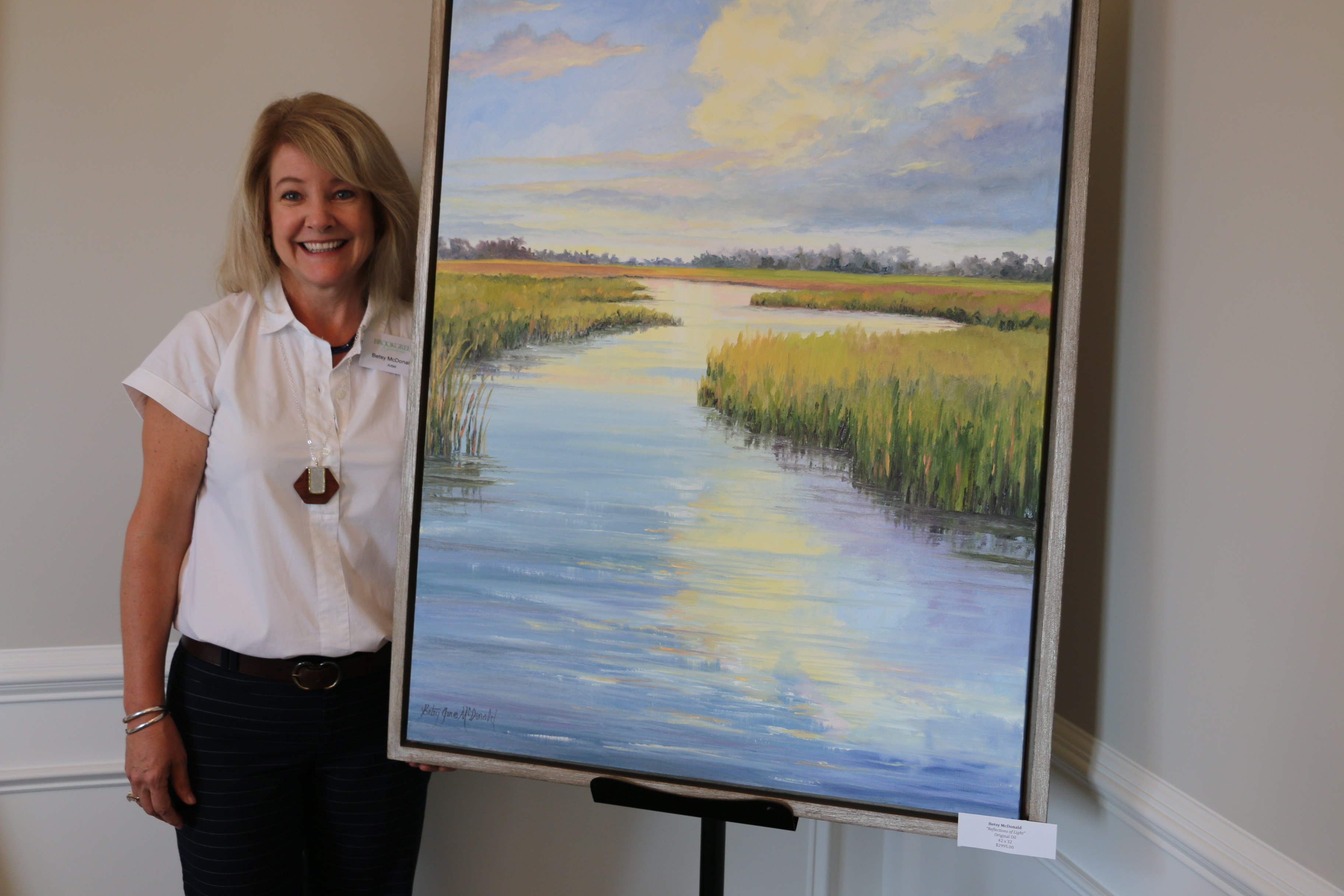 "Artist Betsy McDonald stands beside her oil painting, ""Reflections of Light."""