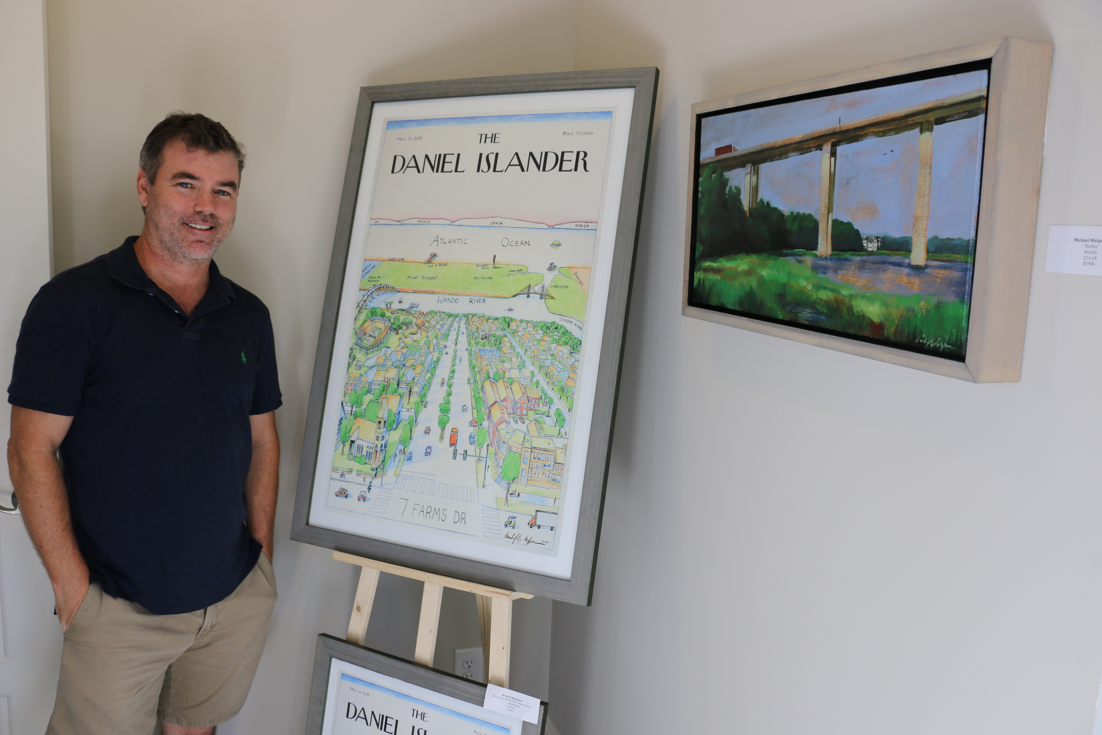 "Artist Michael Mulqueen poses with his popular ""Daniel Islander"" poster print and an acrylic painting depicting the James B. Edwards Bridge over the Wando River."