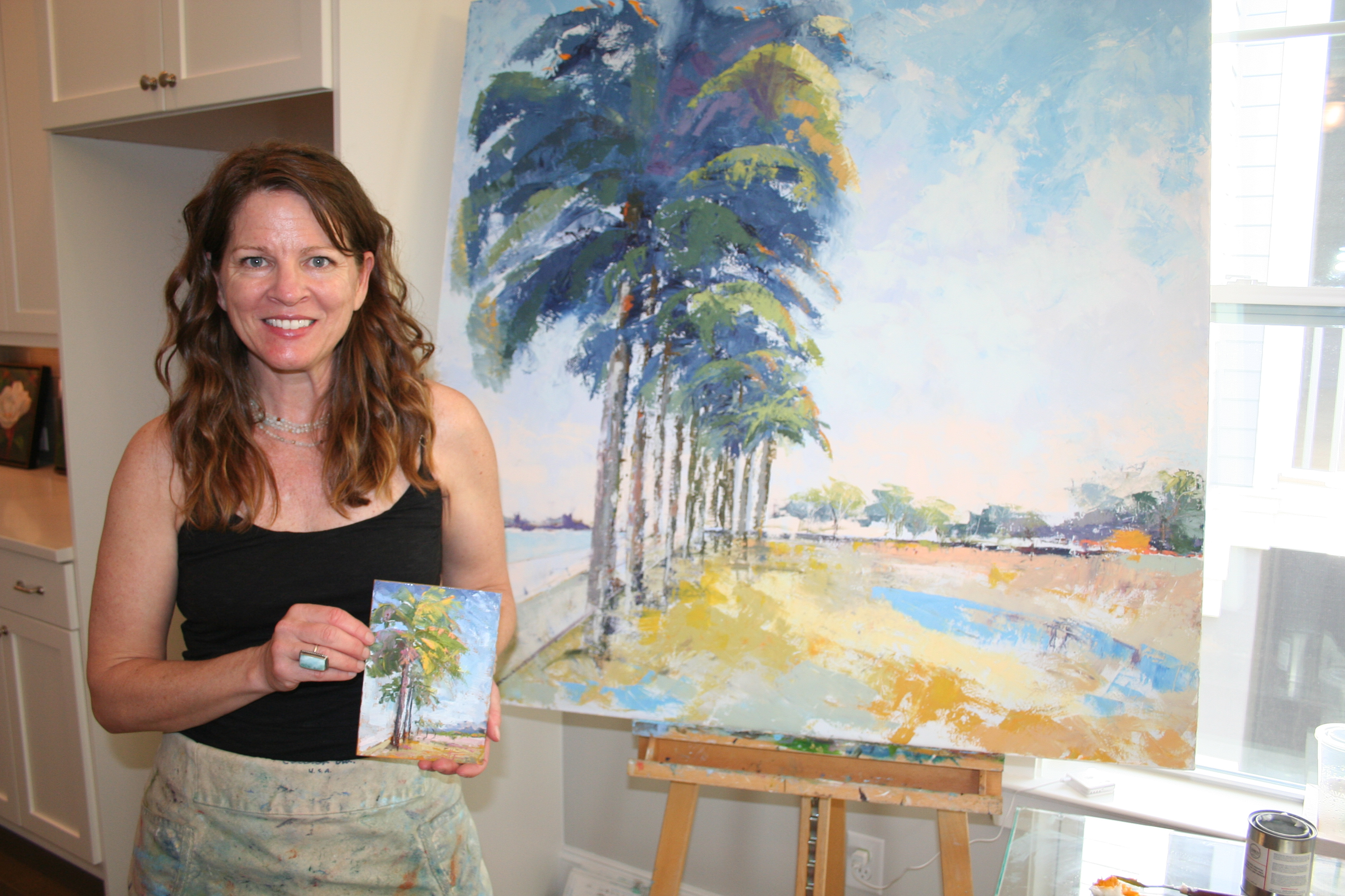 Daniel Island resident Heather Jones (pictured here) organized the pop-up art show and studio event at the open house on April 14. Jones, who is also an artist, worked on finishing this large painting during the festivities!