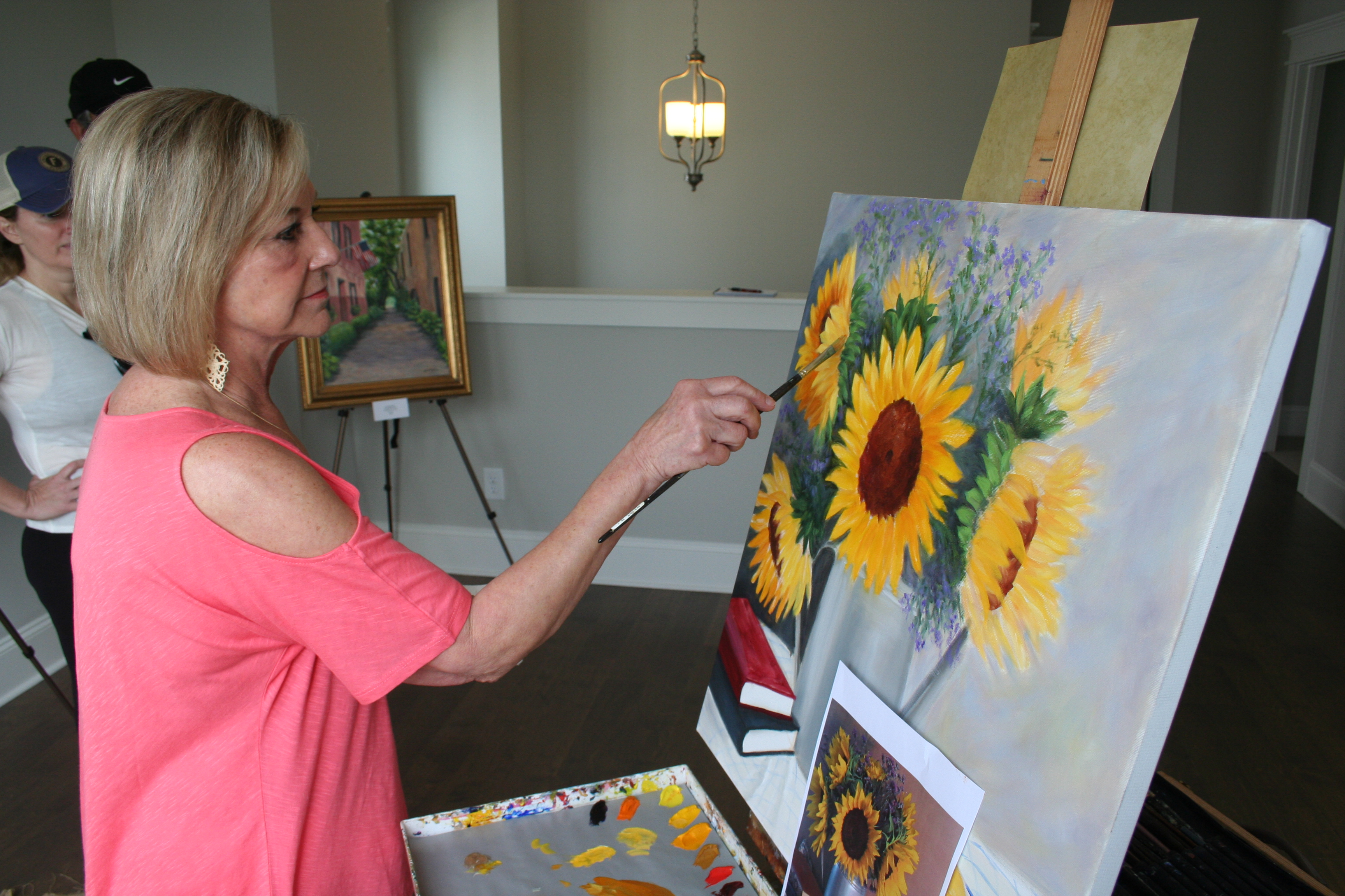 Teresa Jones perfects a painting of sunflowers during an open house at a David Weekley home on Bellona Street last weekend.