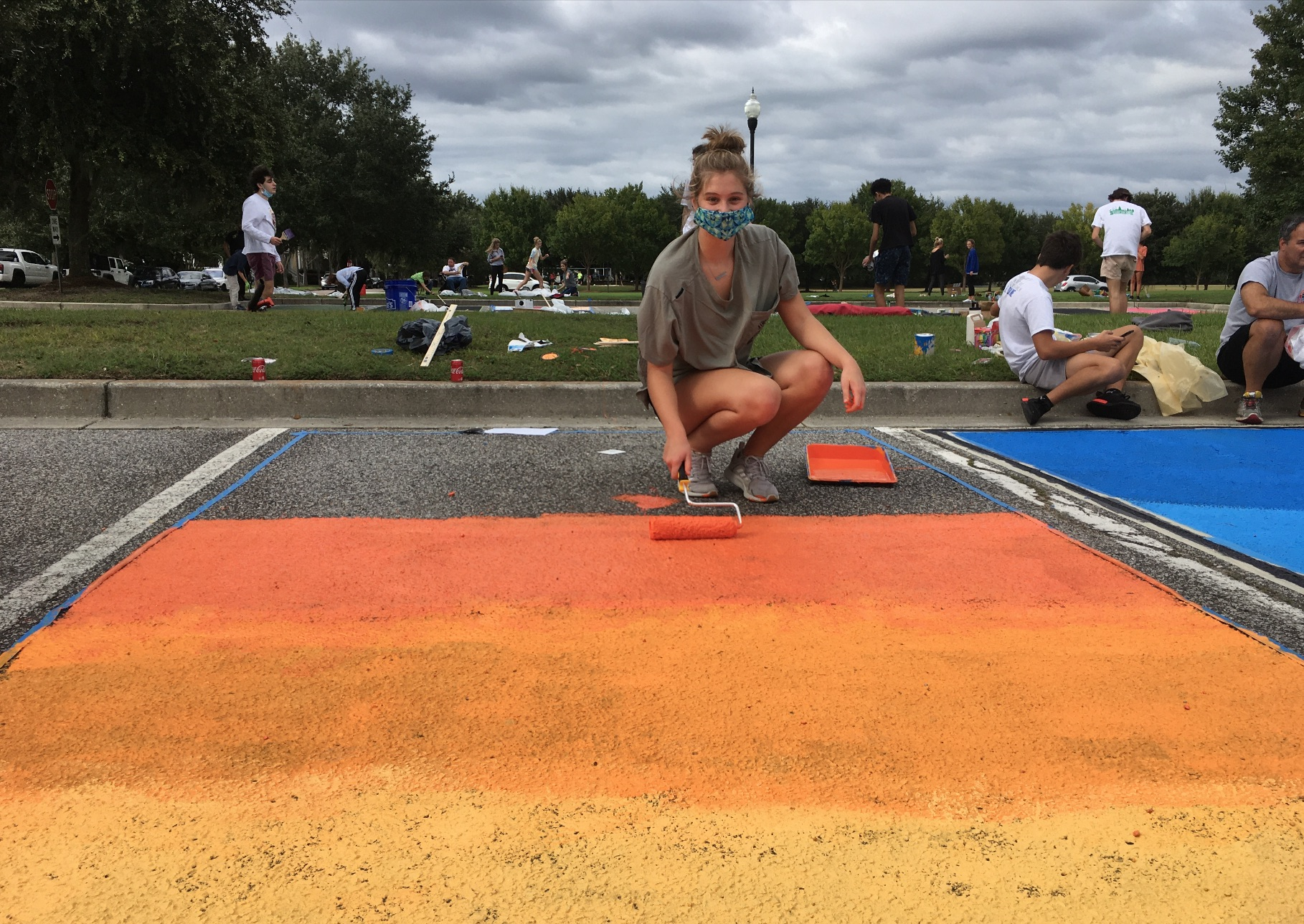 Catherine Grace Soper, 17, painted her parking space with multiple shades of orange, almost like a sunset. Here she displays her colorful creation.